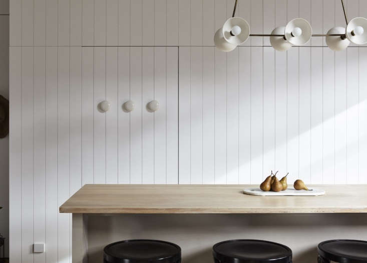 Painted in in Dulux'sLexicon Quarter, wood paneling adds texture in a kitchen in Melbourne, designed by Carole Whiting Interiors Design. Photograph by Jack Shelton.