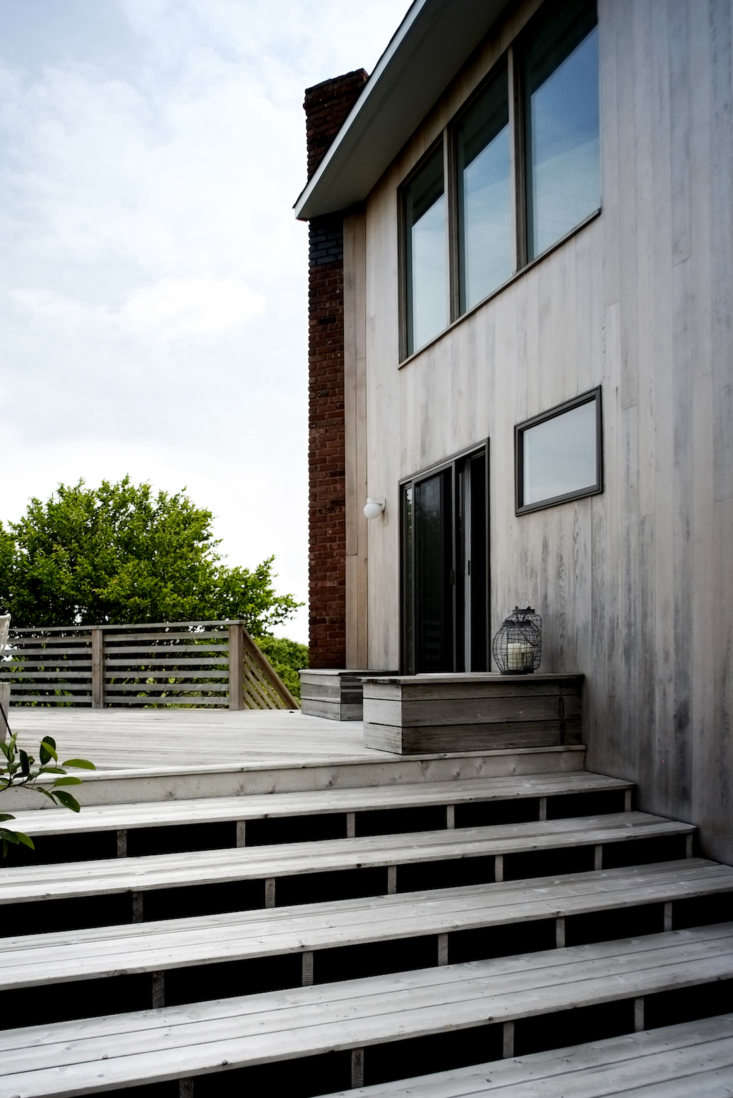 A simple palette for a beach house at the end of a rugged road on the tip of Long Island, New York includes a wooden deck with matching steps, abutting a cedar-sided facade. See more in Hardscaping loading=