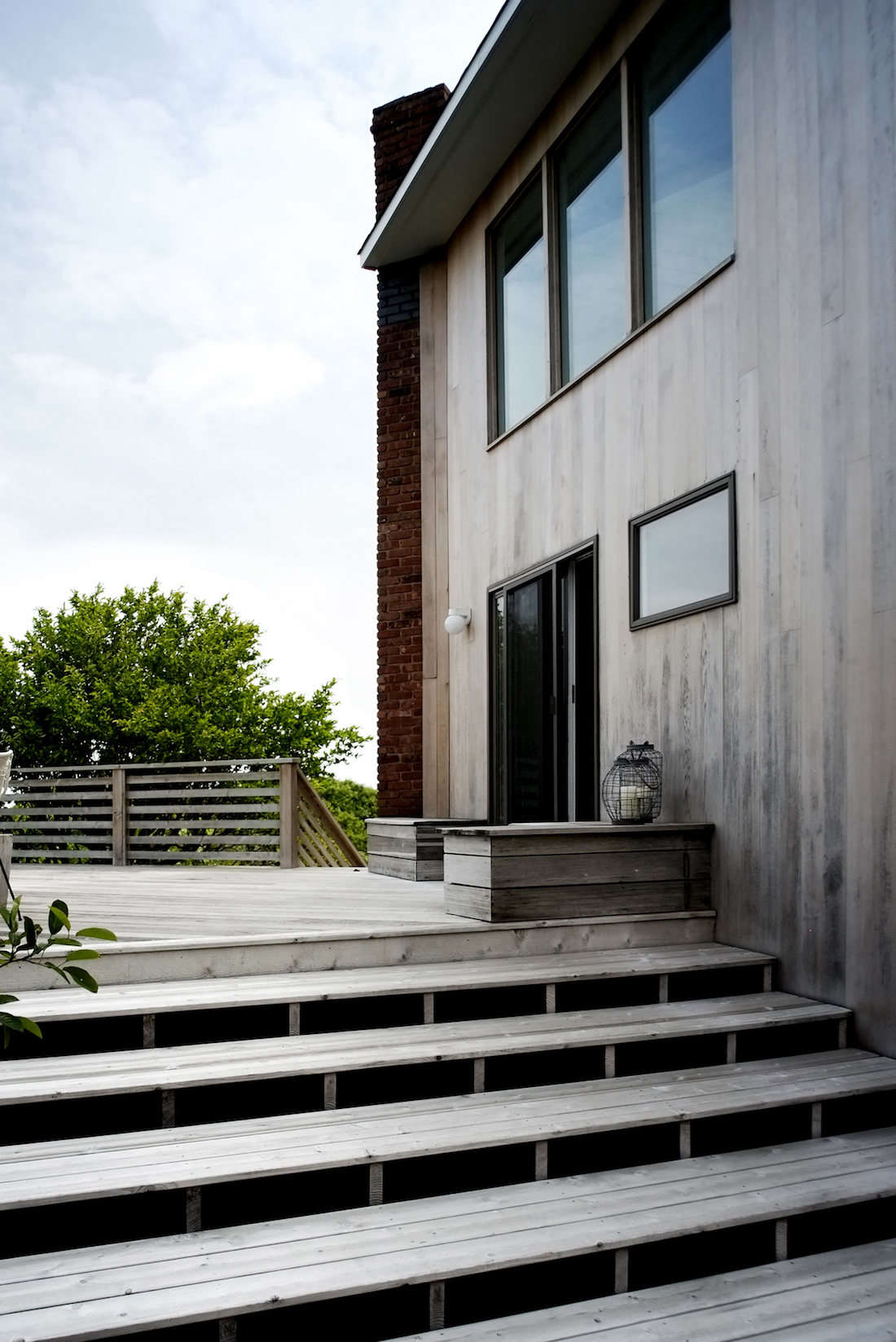 A simple palette for a beach house at the end of a rugged road on the tip of Long Island, New York includes a wooden deck with matching steps, abutting a cedar-sided facade. See more in Hardscaping src=