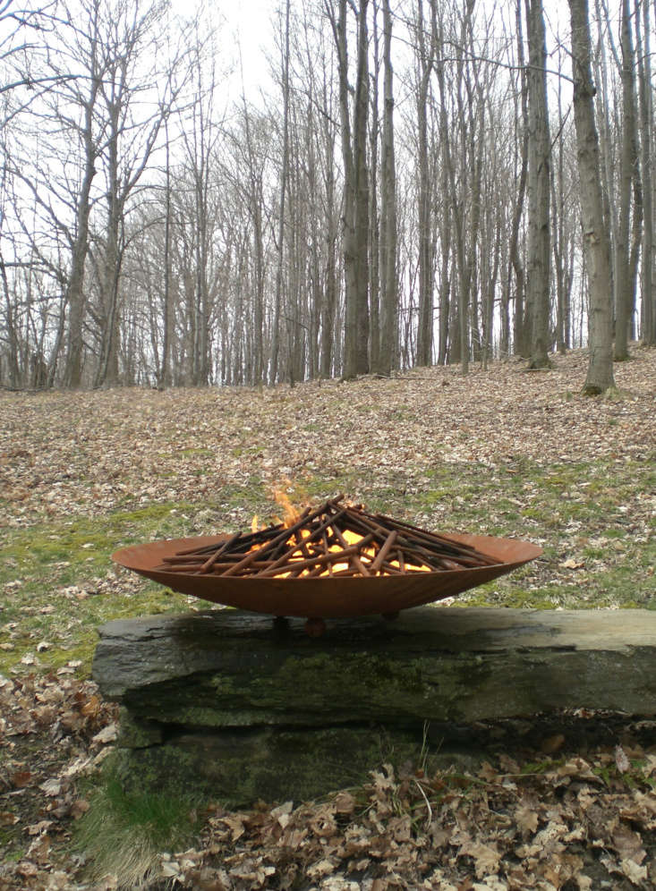 A Corten steel fire bowl with branch inserts.
