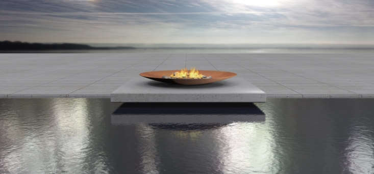 A fire bowl at the edge of a swimming pool.