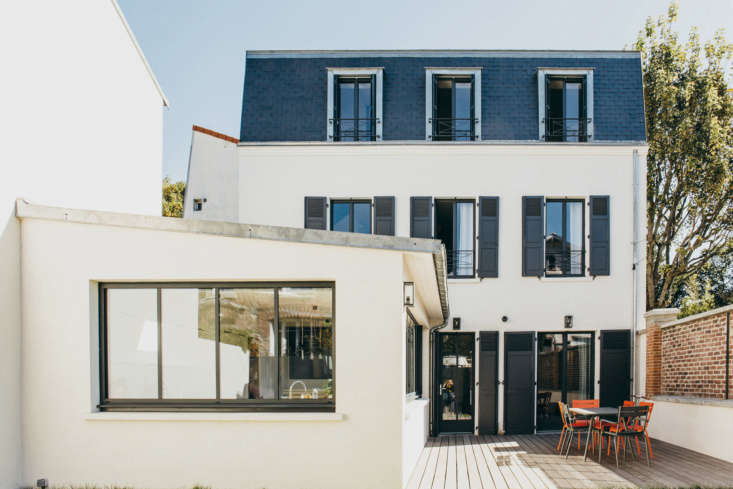 """""""The subtle use of color on an exterior is a great way to give a house a contemporary edge—especially for traditional \19th-century Parisian architecture,"""" designer Camille Hermand explains. """"I like to keep things simple and sophisticated with a soft shade of off-white for walls, and a contrasting rich shade of blue or gray on window frames and shutters. Farrow & Ball's Off Black is a favorite of mine and works particularly well with the cast iron of balustrades."""" Hermand also likes to pair Hague Blue with Strong White, two other Farrow & Ball favorites. (Seen here in a project by Hermand, walls are painted Strong White with Off Black shutters.)"""