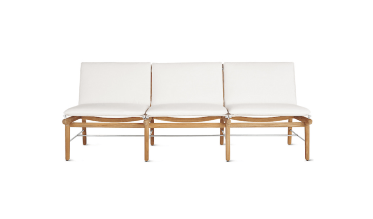 A a 76.5-inch-long Finn Three-Seater Sofa from Danish design house Norm has a teak frame and mildew-resistant Sunbrella cushions (available in white or black); \$\2,795 at Design Within Reach.