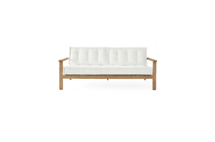 A Cliffside Teak Sofa made of weather-resistant, unfinished Grade A teak has tufted Sunbrella canvas cushions. It is 77.5 inches wide and 30.5 inches high; \$\2,898 from Serena & Lily.
