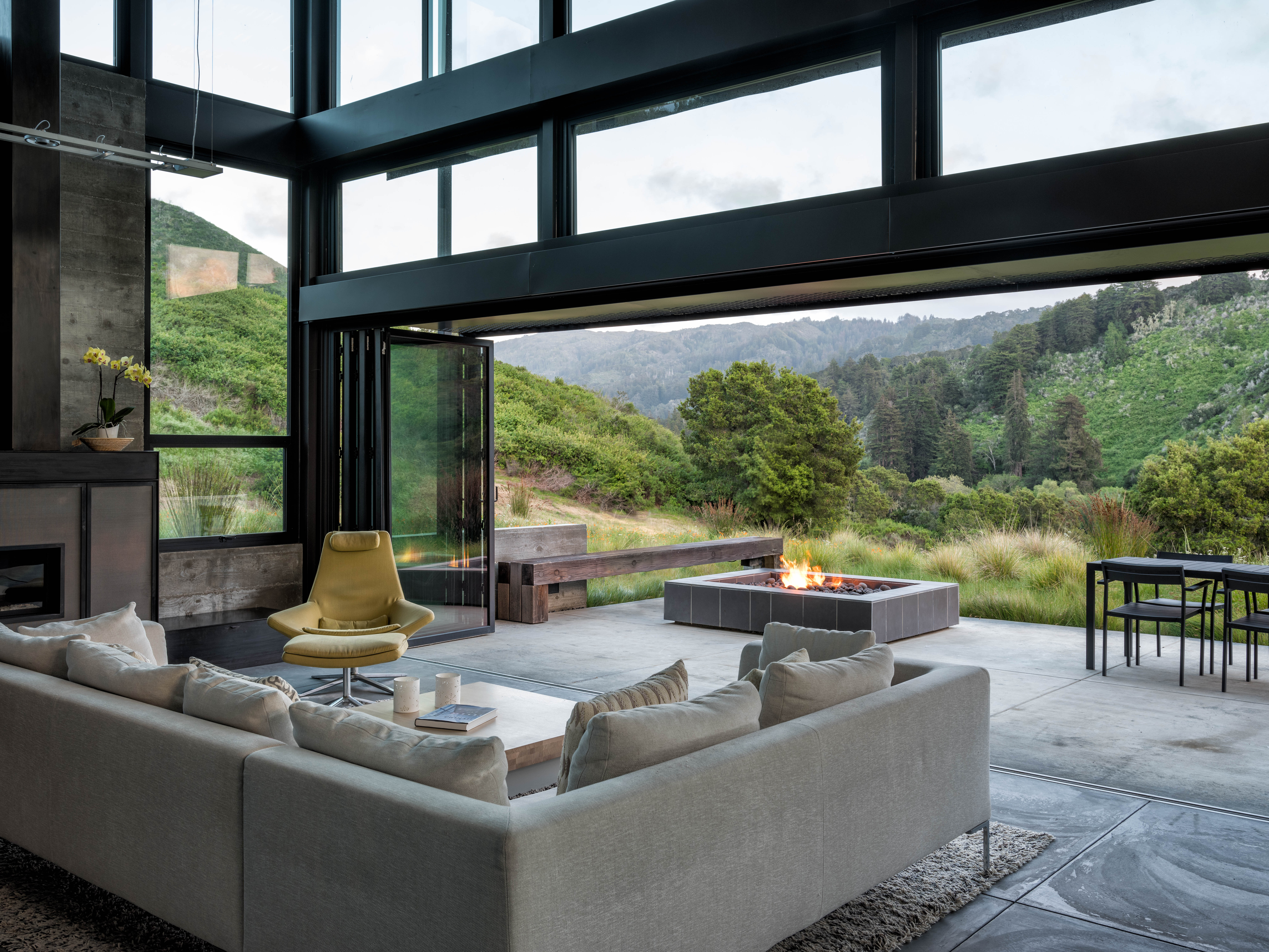 On a patio, a custom fire pit and cedar bench anchor the outdoor living space. At the edge of the patio, Festuca mairei grasses add an airy texture. See growing tips in Festuca: A Field Guide to Planting, Care & Design.