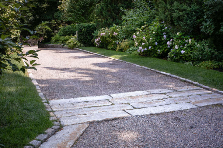 A gravel drive, lined with more salvaged granite, enhances the informal cottage feel. Here a lush border of shade-loving plants create a textured privacy screen from the neighboring house.