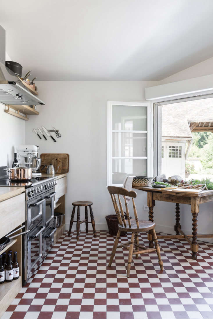 Solid oak drawers and open storage complement a traditional checked kitchen floor. Photograph by Romain Richard.