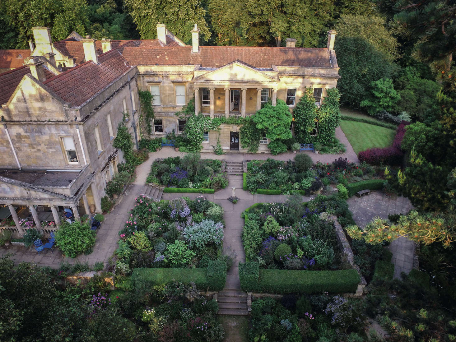 """""""An aerial view shows the strong structure and shapes of the planting in the Four Squares. Encircling the lawn to one side of the house is the brilliant hedge of Berberis thunbergii f. atropurpurea 'Rose Glow',"""" writes Berridge."""