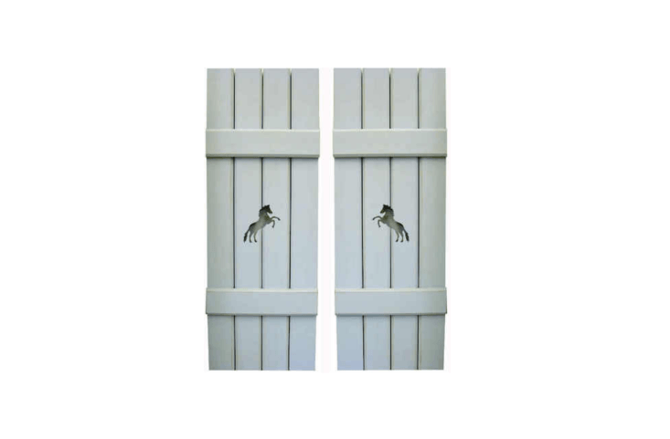 Wooden shutters embellished with horses cutouts can add whimsy to a stone facade. See more designs at Shuttercraft.