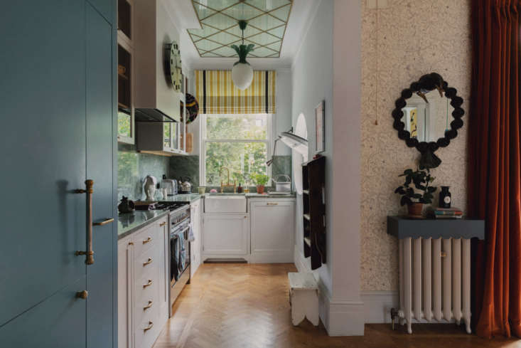 Designer Beata Heuman chose panels and hardware for the refrigerator that look more like a piece of furniture than an appliance, since the kitchen is attached to the dining room. Photograph courtesy of The Modern House, from A Rising Star's Spirited London Home: 'Every Room Should Sing!