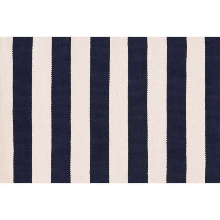 A bold classic, the Catamaran Stripe Outdoor Rug by Dash and Albert, shown in navy and cream, is $loading=