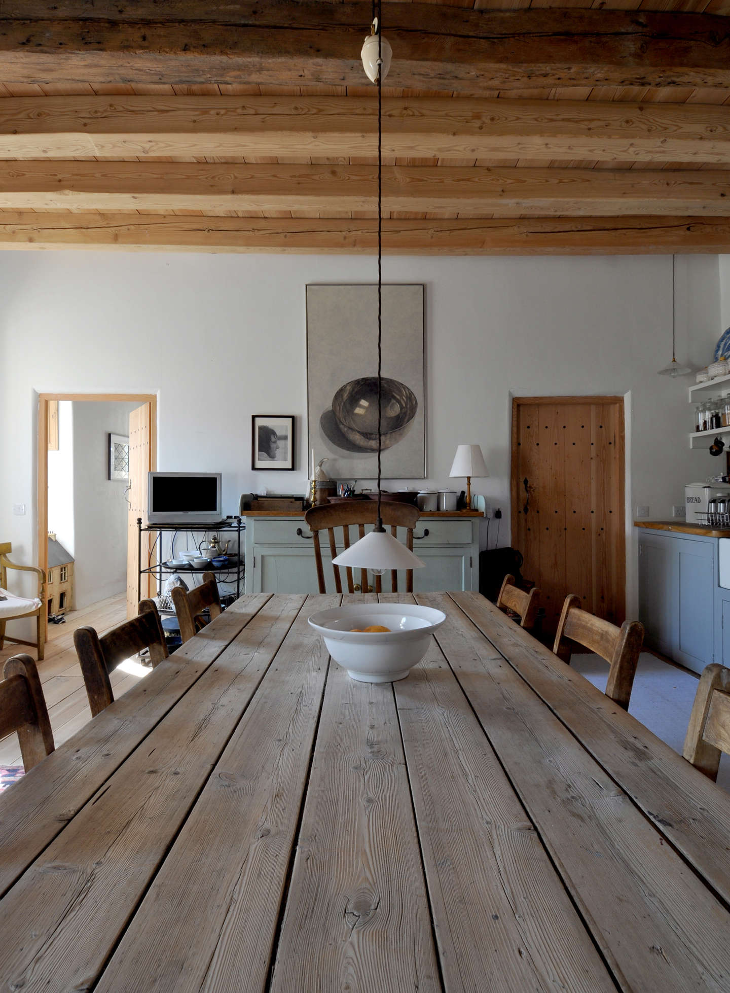 Smack-dab in the middle of this kitchen: an antique dining table with a pulley pendant light hovering over it. Photograph courtesy of Groves-Raines Architects, from Lamb's House: A Masterful Restoration of a th Century Home (Once Visited by Mary Queen of Scots).