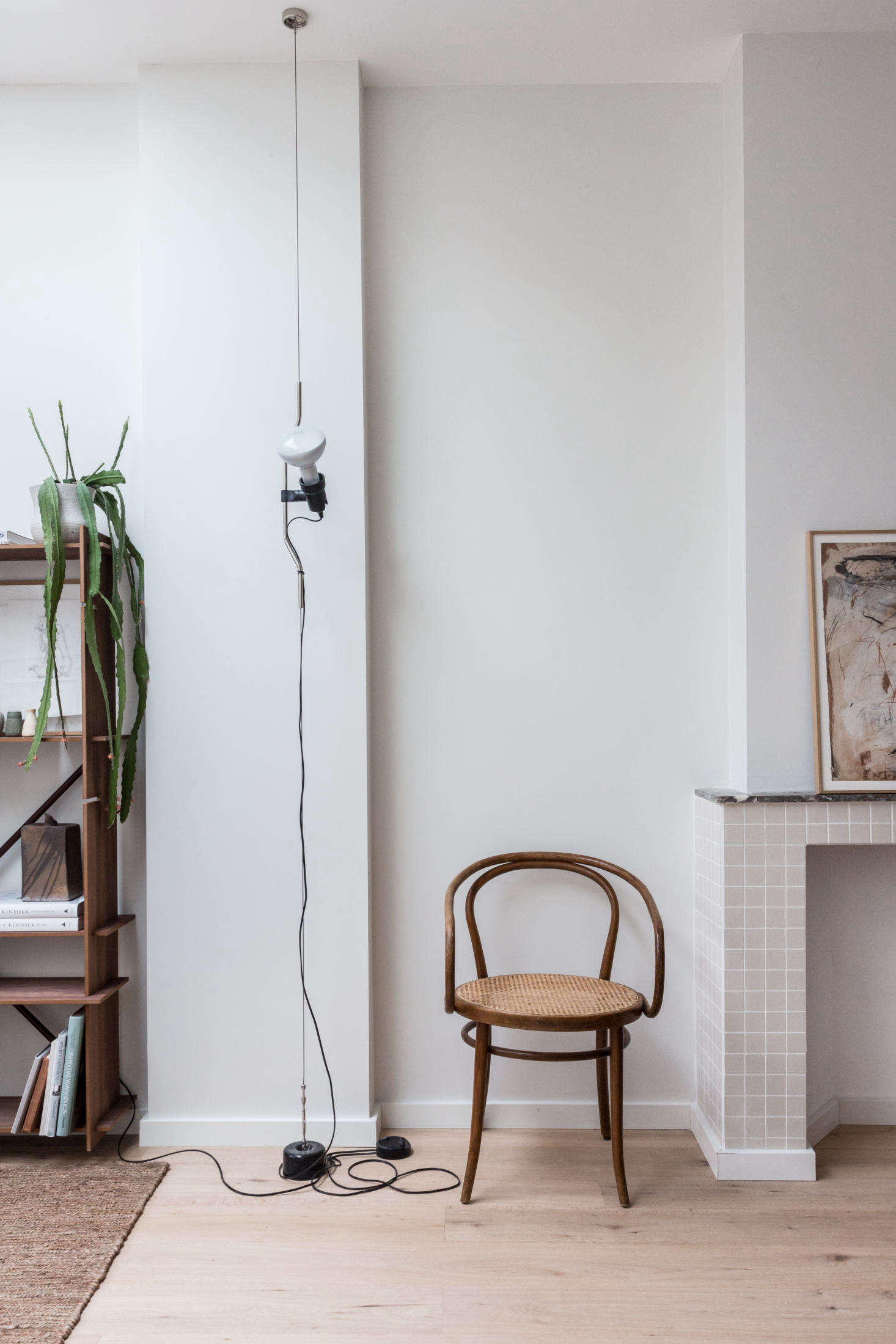A vintage Thonet armchair sits pretty next to the very modern Parentesi Suspension Light. Photograph by Holly Marder, from Steal This Look: An Interior Designer's High/Low Scandi Living Room, Ikea Sofa included.