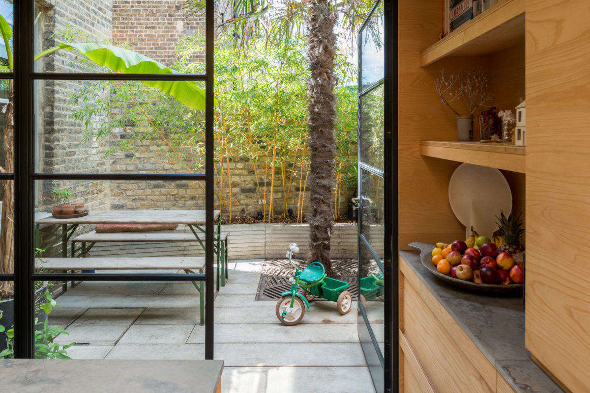 A biergarten table and bench set is a chic classic for a casual patio, and this one, with green legs, is just about perfect. Photograph courtesy of The Modern House, from Kitchen of the Week: A London Architect's Sky-Lit Compact Kitchen.