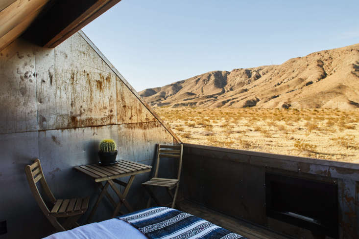 At Joshua Tree Folly, a little guesthouse off the beaten path in Southern California, an open-air bedroom awaits. Photograph by Sam Frost via Cohesion Studio, from Desert Dream: An Architect-Designed, Off-the Grid Cabin in Joshua Tree.