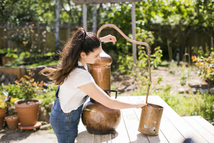 Justine with her functional and aesthetically pleasing copper still. She makes hydrosols or flower waters weekly in the summer months, using techniques dating back \1,000 years.