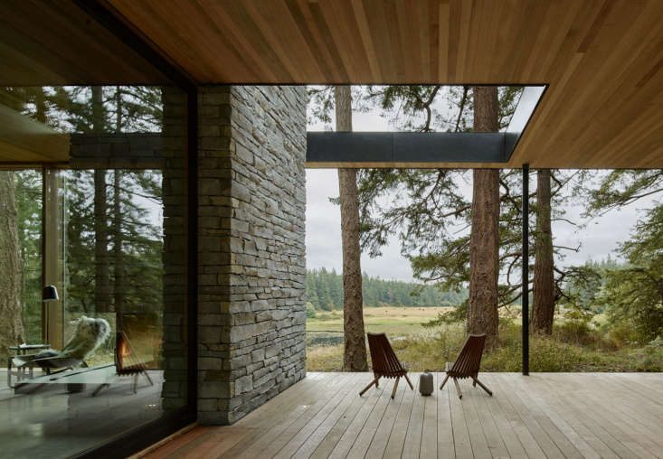 An indoor fireplace transitions into the exterior stone wall of a picturesque deck by mwworks. Photograph by Kevin Scott, courtesy of mwworks, from Outside In: A Multi-Generational Retreat on Whidbey Island Welcomes Nature Inside.