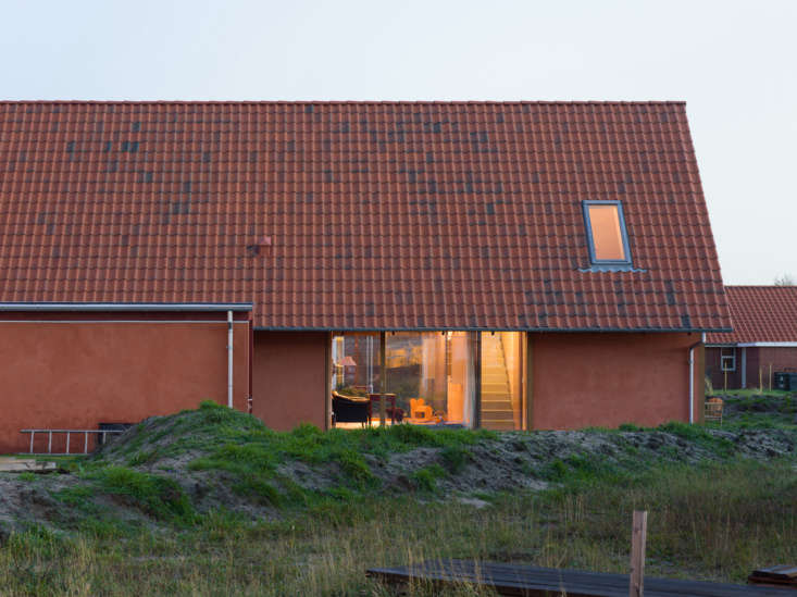 A red clay-tiled roof on a minimalist long house. Photograph by Hampus Berndtson, courtesy ofLeschow & Pihlmann, from Raw Materials: A Minimalist Longhouse on Denmark's Fanø Island, Starring Plywood and Clay.