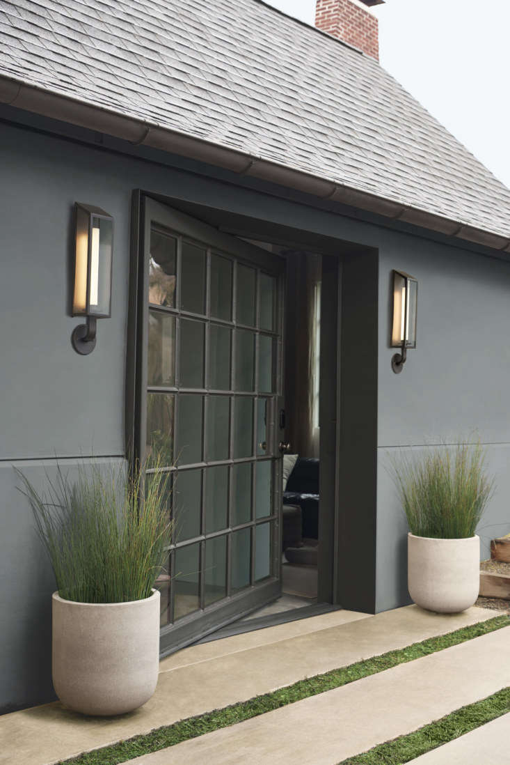 Draw attention to a doorway with symmetrical sconces. Here, twin Lombard Lantern LED Wall Sconces in oil-rubbed bronze ($649 each) frame an architectural glass door.