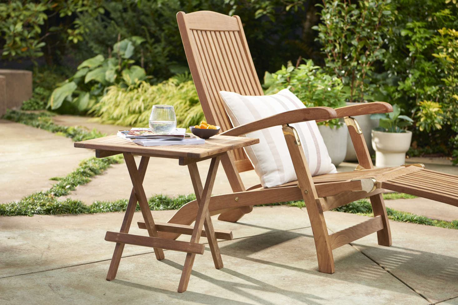 Even tiny outdoor spaces can turn into mini oases with a single Teak & Brass Folding Lounge Chair ($src=