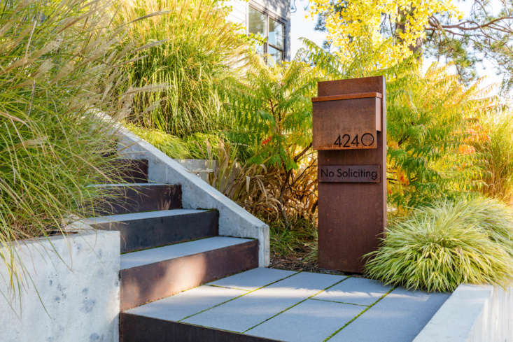 A new street-level custom mailbox clearly announces the house&#8\2\17;s presence. Steel and concrete steps lead the way to the front door.