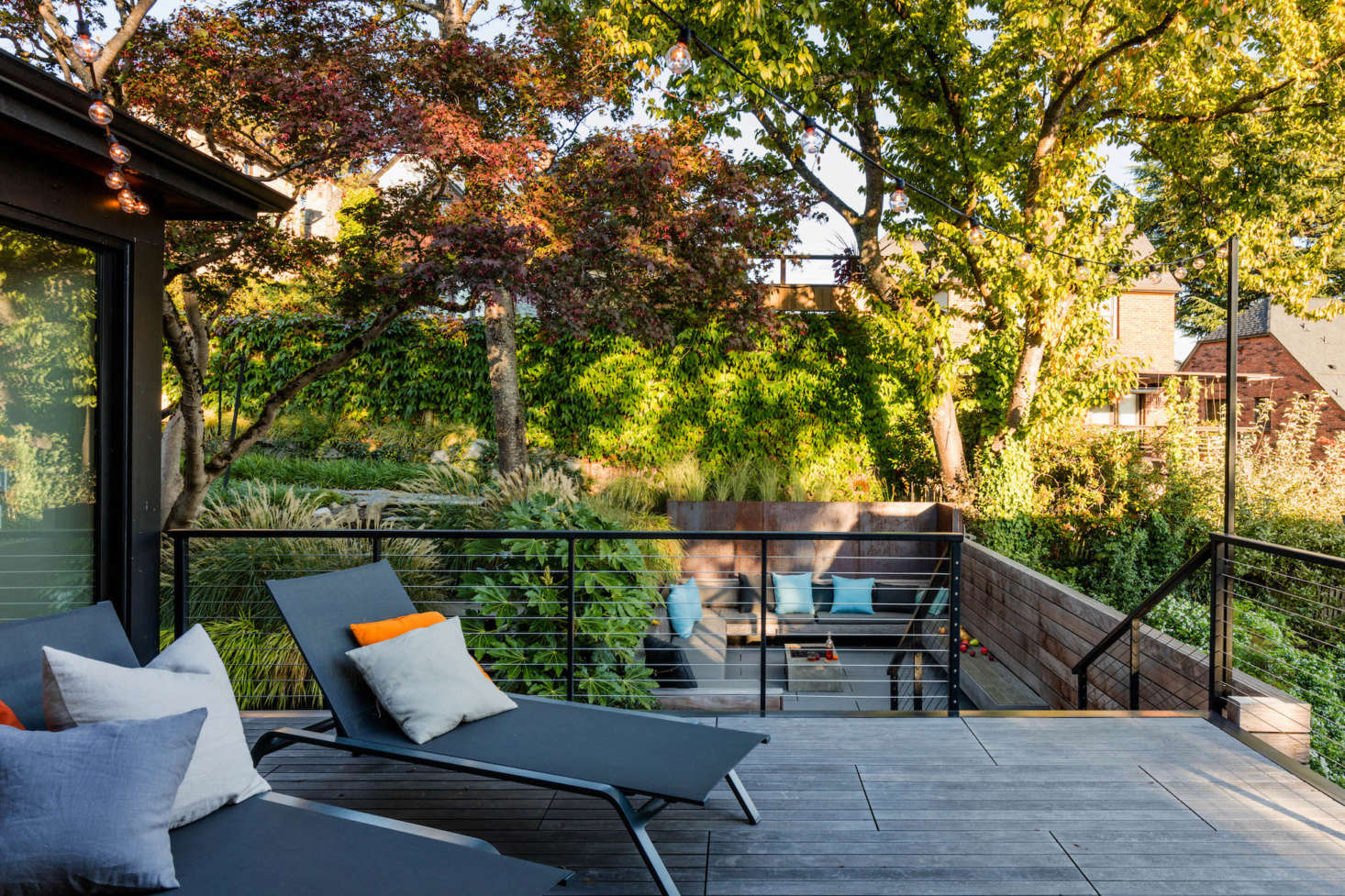In the back of the house, the kitchen and dining area opens out onto an ipe hardwood deck that steps down to a larger outdoor living room below.