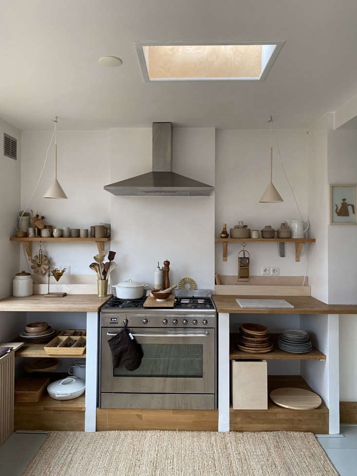 Two petite conical pendants offer stylish task lighting in this hand-built kitchen in the Netherlands. Photograph by Tinta Luhrman, from Carved in Wood: The Bespoke Home of a Self-Taught Carpenter and an Interior Designer.