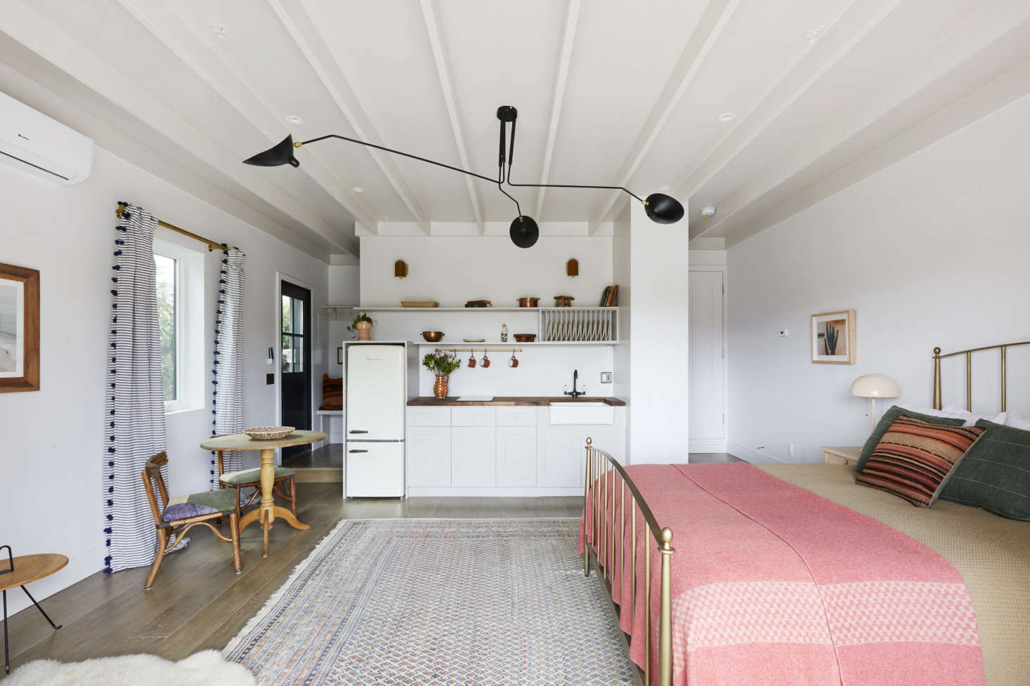 In place of two cars, the approximately 400 square foot garage now has a kitchen, eating area, and bed. See more of this inspired conversion in Found Space: A Garage-Turned-Cottage in LA. Photograph by Jessica Alexander, courtesy of Allprace Properties.