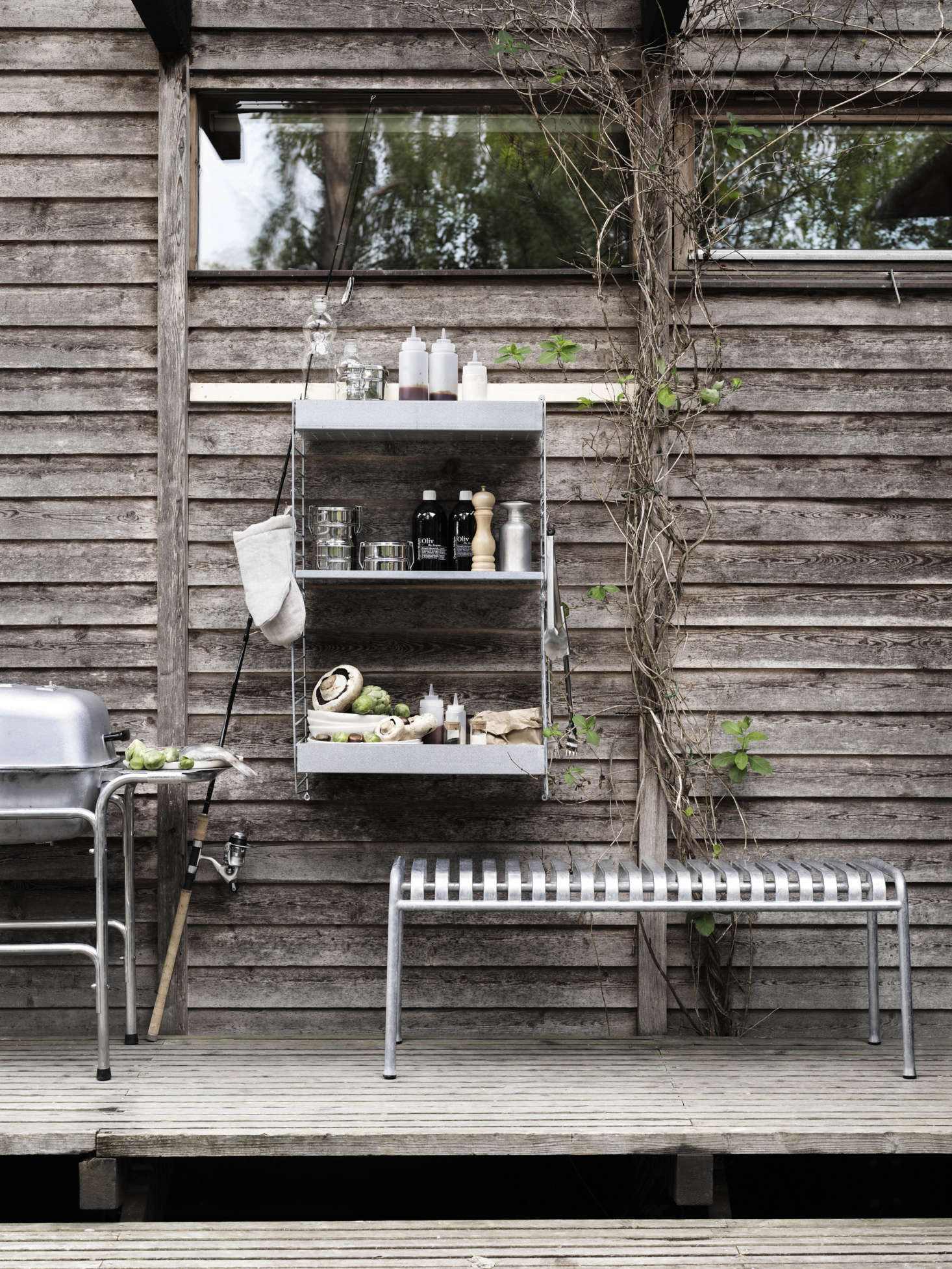 The shelves make an ideal companion to an outdoor grill. Metal hooks are available for hanging tools and accessories.