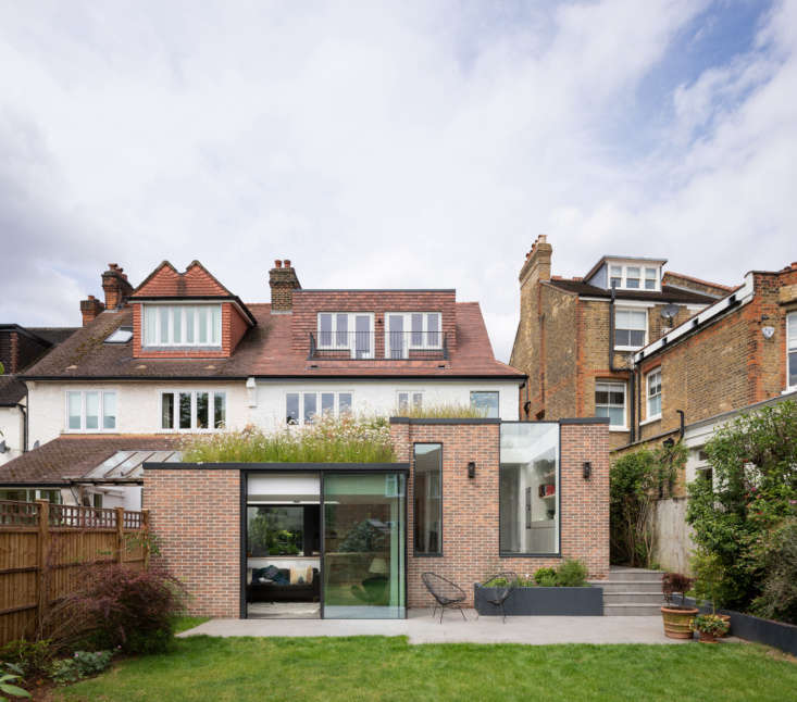 Behind the modern addition, which houses the kitchen and dining areas, is the original home, built in the early 00s. The residence is in South West London, a conservation area close to the River Thames.