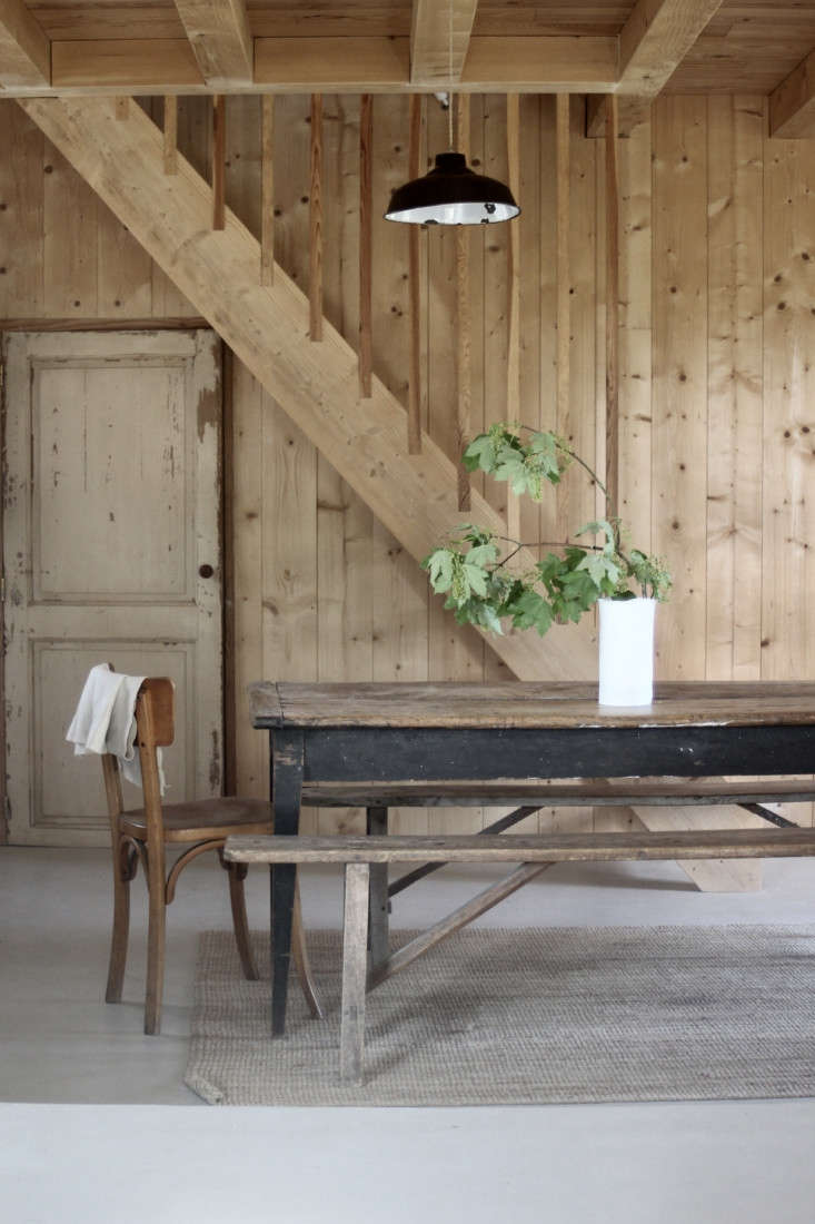 In a minimalist-rustic cabin in France, a branch of foliage offers just the right amount of color. Photograph by Jean Hay de Slade, courtesy of Epure, from Creative Compound: A Ceramic Artist Couple at Home and Work in the French Countryside.