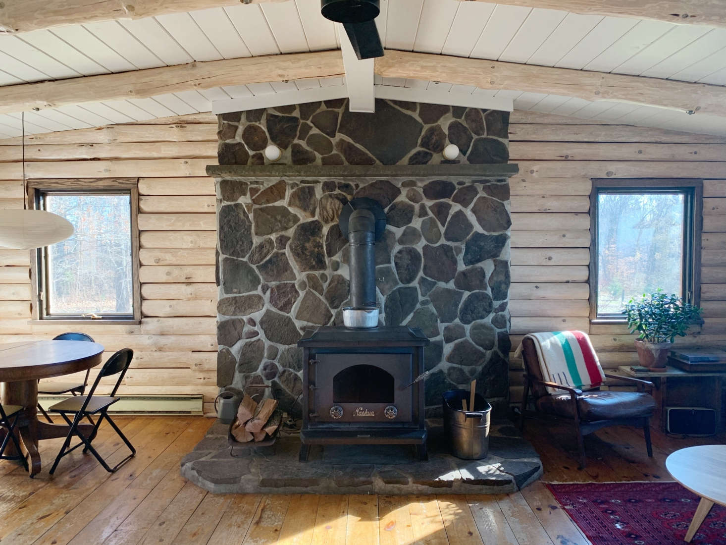 This dark log cabin interior gets the Scandi treatment in Before and After: A Couple's DIY Cabin Upstate, Redone During Quarantine.