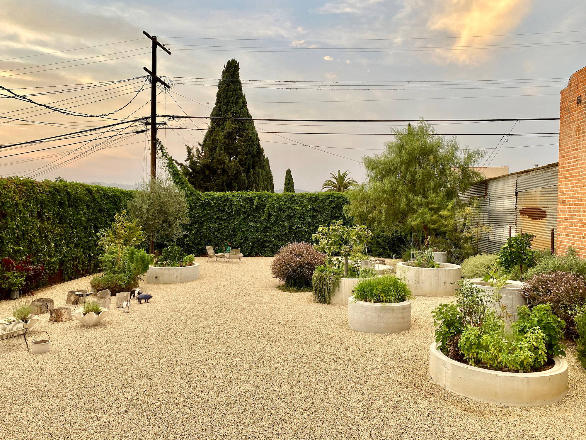 """The gravel garden oasis that now greets visitors. """"I was interested in creating a more sculptural setting that would provide a different type of edible garden experience. Since I planned on hosting families with kids, I had imagined large, soft, round shapes that children might enjoy—the scale, curves, and recesses of hidden space around which to play and plant."""""""