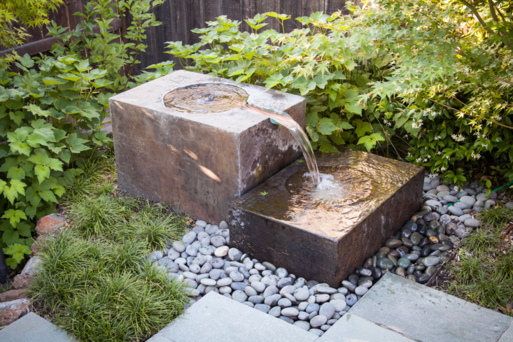 The recirculating fountain, constructed of two blocks, adds the soothing sound of moving water, creates an interesting focal point, and provides a bathing and drinking spot for local birds. Mondo grass is the perfect undemanding ground cover as it is both lush-looking and water-wise.