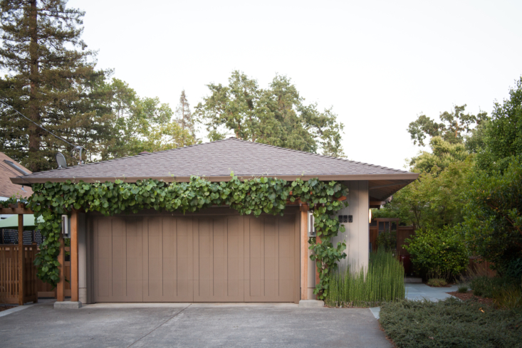 A lush grape vine framing the garage hints at the green oasis in the back.