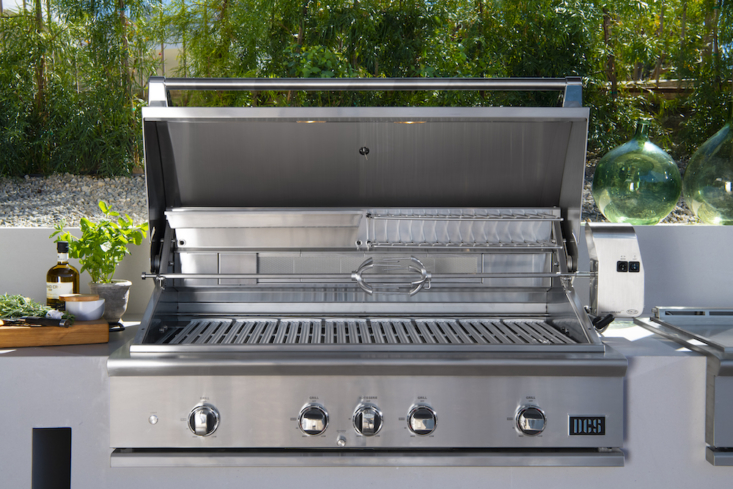 The 48″ Grill, Rotisserie and Charcoal is designed to be an all-in-one outdoor cooking appliance, with intuitive built-in lighting to illuminate your cookspace (perfect for after dark); an easy-lift hood that can be maneuvered with one hand; an extra cooking area above the main grill space that can accommodate a broiling pan for slow-roasting, making sauces, or keeping dishes warm; a built-in charcoal smoker tray; and an infrared rotisserie burner. (The rotisserie rod is cleverly stored under the drip pan handle.)