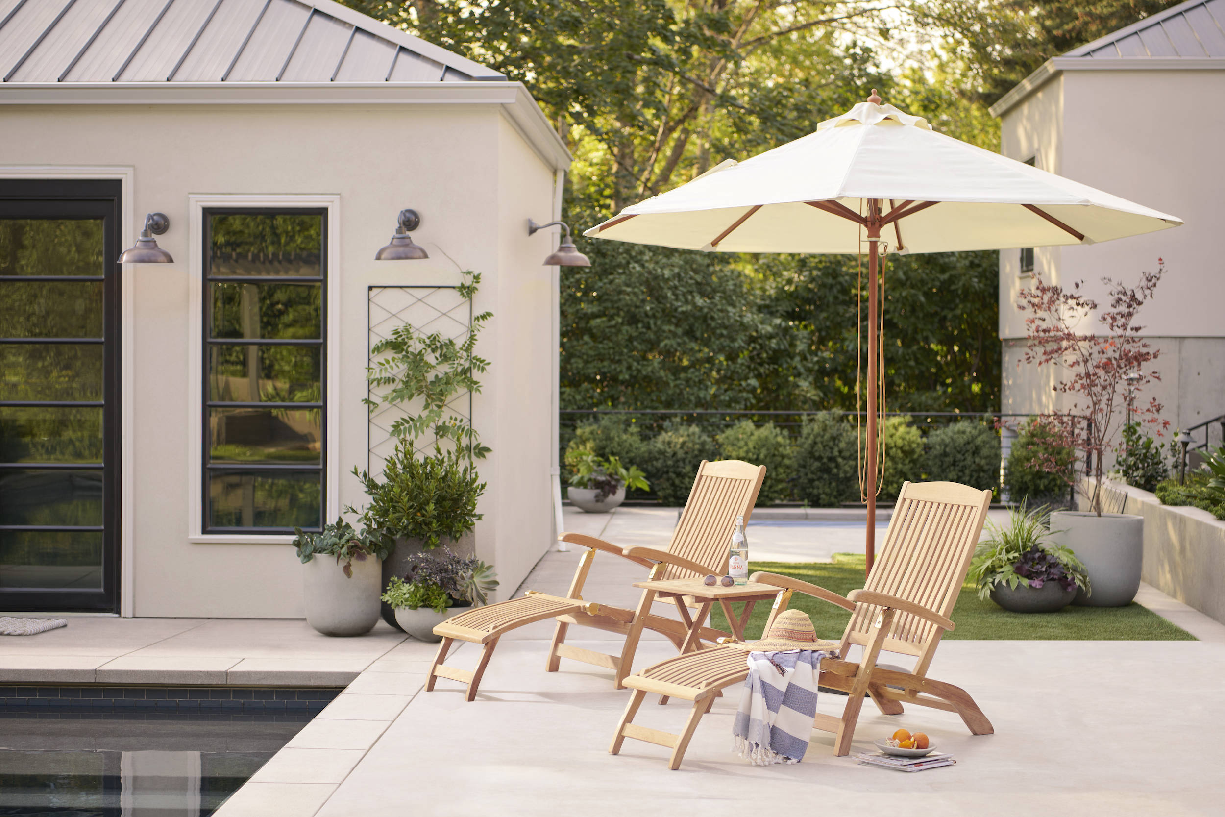The perfect warm-weather change of scenery: lounging outdoors. The Teak & Brass Folding Lounge Chairs ($src=