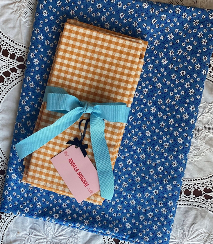 This tablecloth and ochre gingham napkin set would be perfect for an outdoor meal. See The Al Fresco Summer Table: Italian Linens and Candles from Angela Mugnai.
