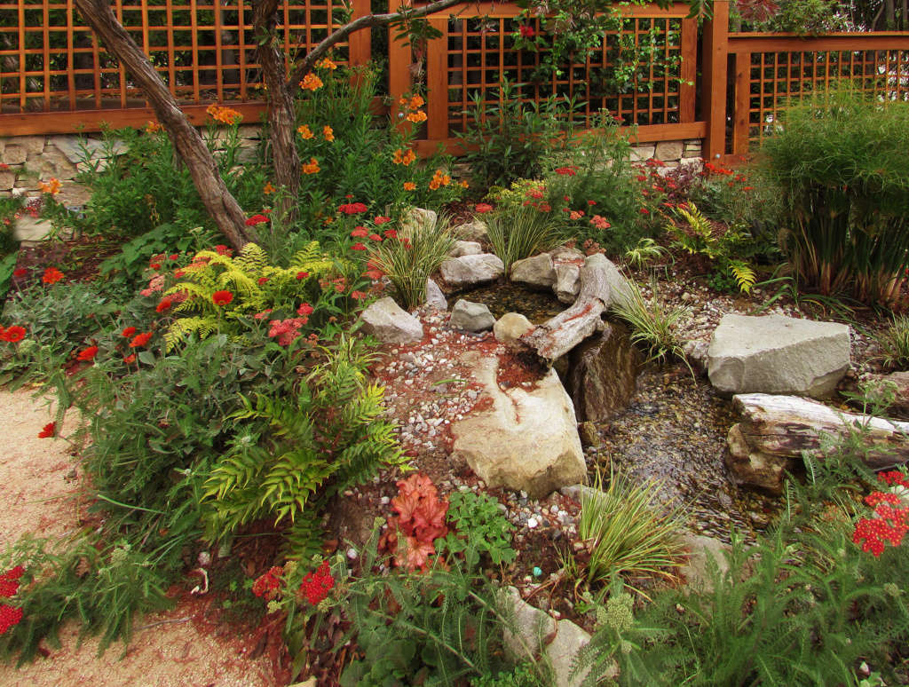 A Waterfall Flows Down the Levels of the Garden Into a Fish Pond Below
