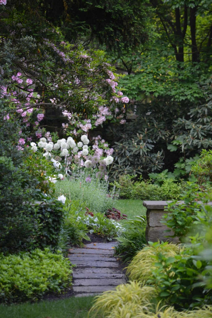 Serene Oasis, a tranquil border of flowers and shrubs create a stunning retreat.